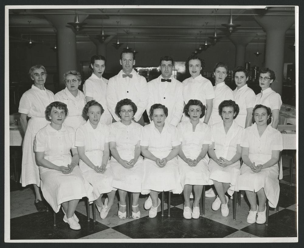 Une photo de groupe officielle), sept femmes sont assises à l'avant-plan. Debout derrière elles, on voit sept autres femmes et deux hommes. Tous portent des uniformes blancs.
