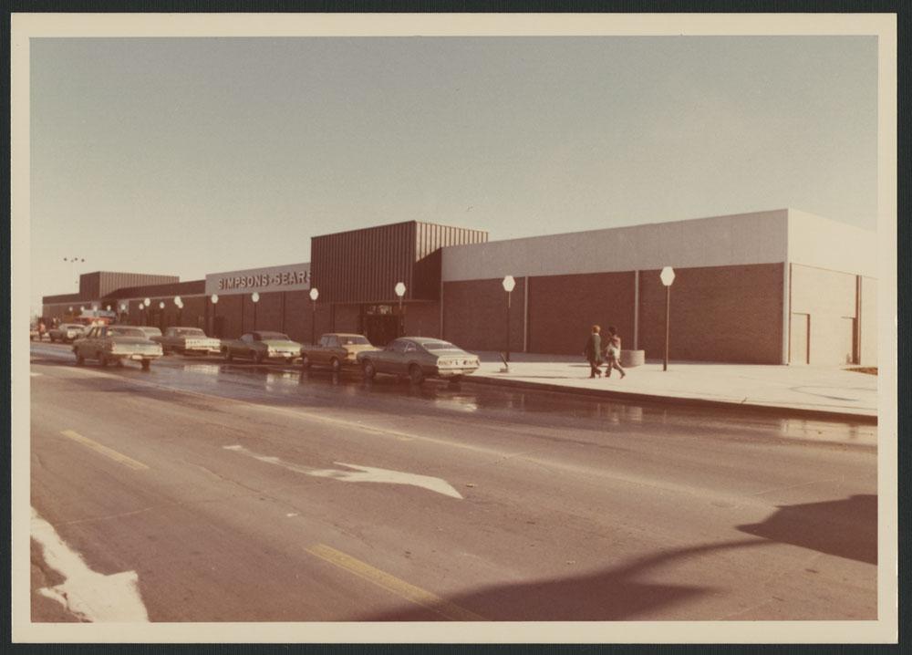 Photos couleur montrant l'extérieur du centre commercial Les Galeries de Hull à Gatineau, au Québec. La photo extérieure montre des voitures stationnées en bordure de la rue, et des gens marchant sur le trottoir; on peut voir « Simpsons-Sears » sur la façade du bâtiment