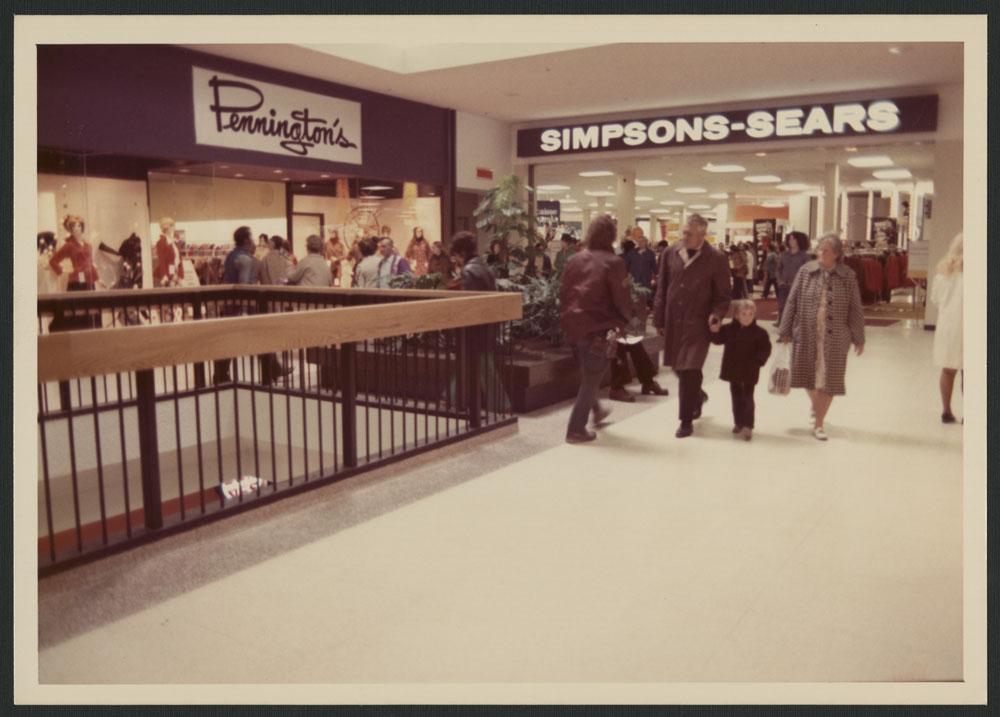 La photo intérieure montre des clients à l'étage supérieur du centre commercial, et les affiches des magasins Pennington's et Simpsons-Sears.