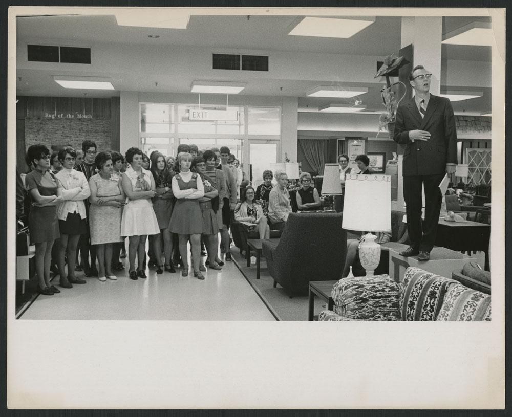 Photo noir et blanc d'un homme debout sur une table, en train de s'adresser à un groupe de femmes.