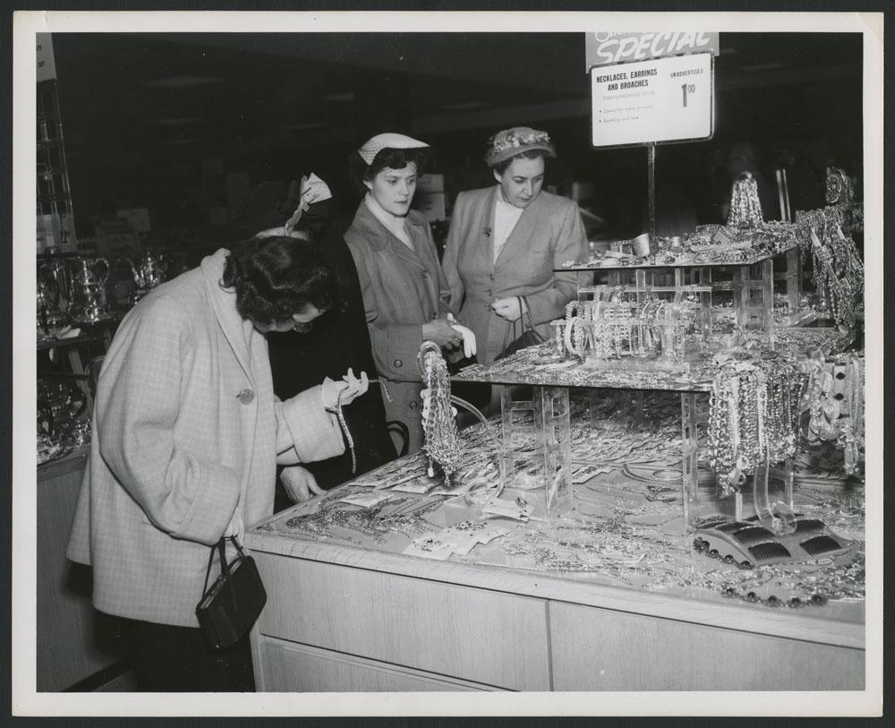 Photo noir et blanc de quatre femmes examinant des bijoux sur le présentoir d'un grand magasin. Une affiche indique « Special: Necklaces, Earrings and Broaches, $1.00. » [Spécial : Colliers, boucles d'oreilles et broches, 1 $ »]