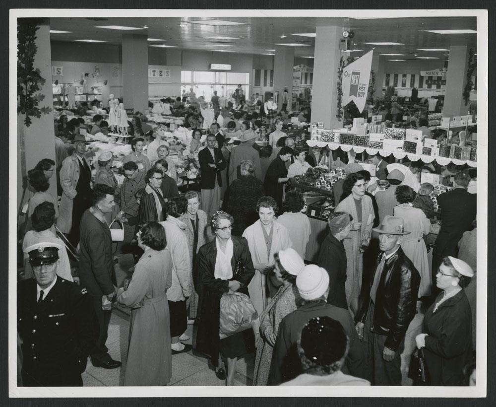 Photo noir et blanc montrant une foule dans un magasin à rayons, avec un gardien de sécurité à l'avant-plan, à gauche.