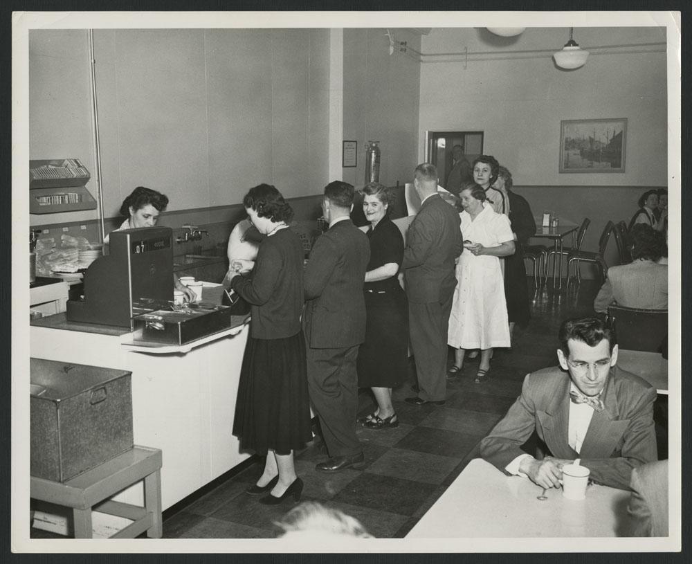 Photo noir et blanc montrent le personnel de la cafétéria d'un grand magasin. On voit des clients faire la file pour payer leurs consommations à la caissière; à l'avant-plan, un homme est assis à une table, un café à la main