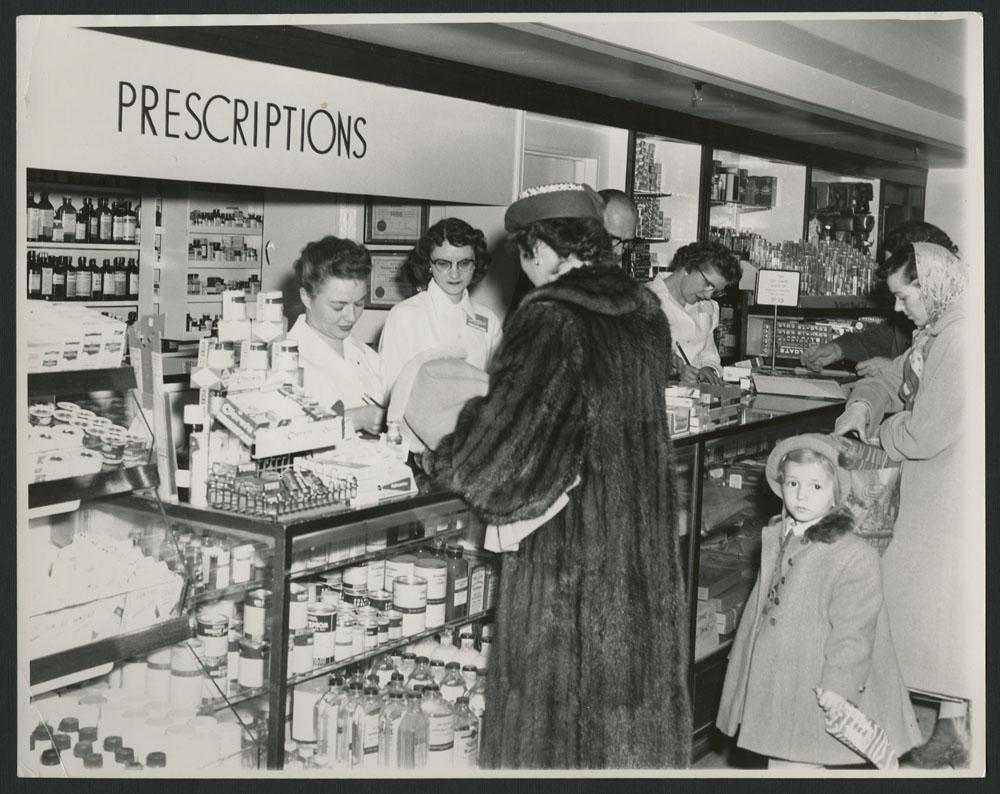 Photo noir et blanc montrant trois femmes et un enfant devant un comptoir de pharmacie. Trois autres femmes sont debout derrière le comptoir. Au-dessus d'elles, un écriteau indique « Prescriptions » [Ordonnances].