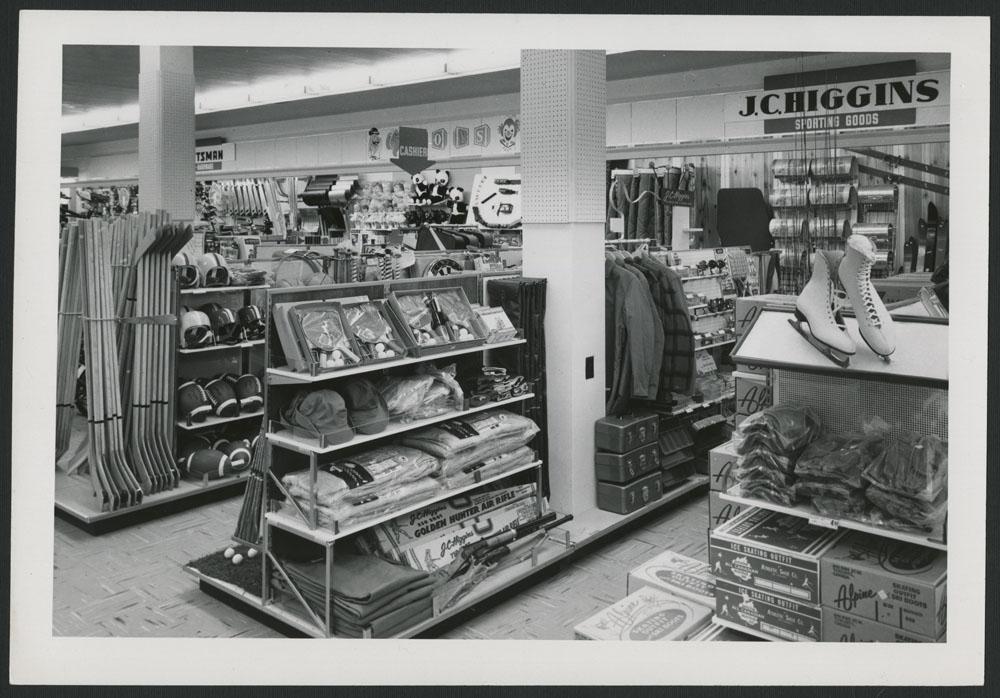 Photo noir et blanc du rayon des sports d'un grand magasin, où l'on peut voir des bâtons de hockey, des vêtements, des cannes à pêche et des patins à glace sur des tablettes.