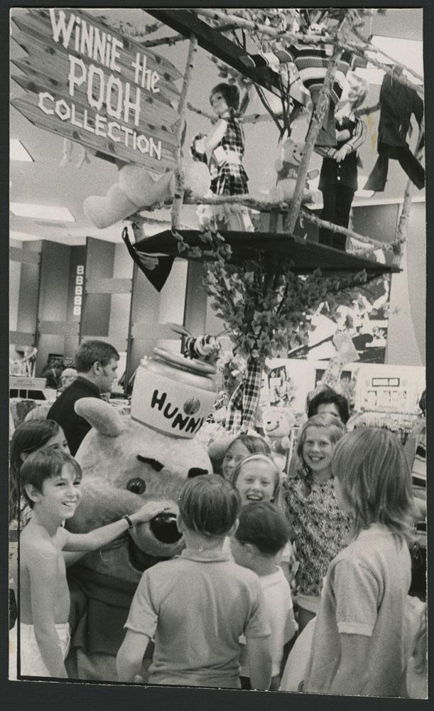 Photo noir et blanc montrant des enfants rassemblés autour d'une mascotte de Winnie l'ourson. À l'arrière-plan, on voit une cabane dans un arbre, avec un écriteau indiquant « Winnie-the-Pooh Collection » [La collection Winnie l'ourson].