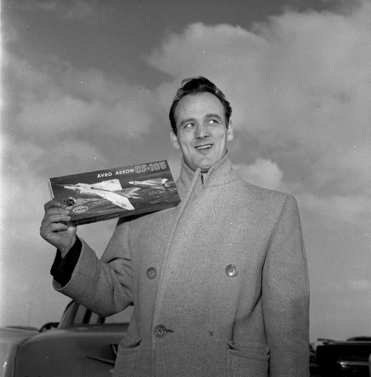 Photo noir et blanc d'un homme tenant la boîte d'une maquette d'avion.