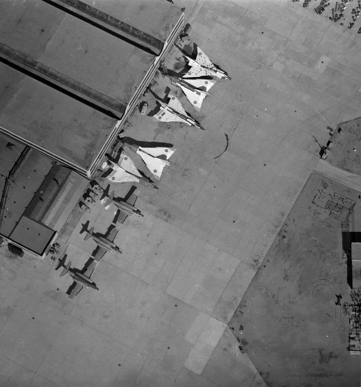 Photo noir et blanc de huit avions stationnés devant un bâtiment, vus depuis les airs.
