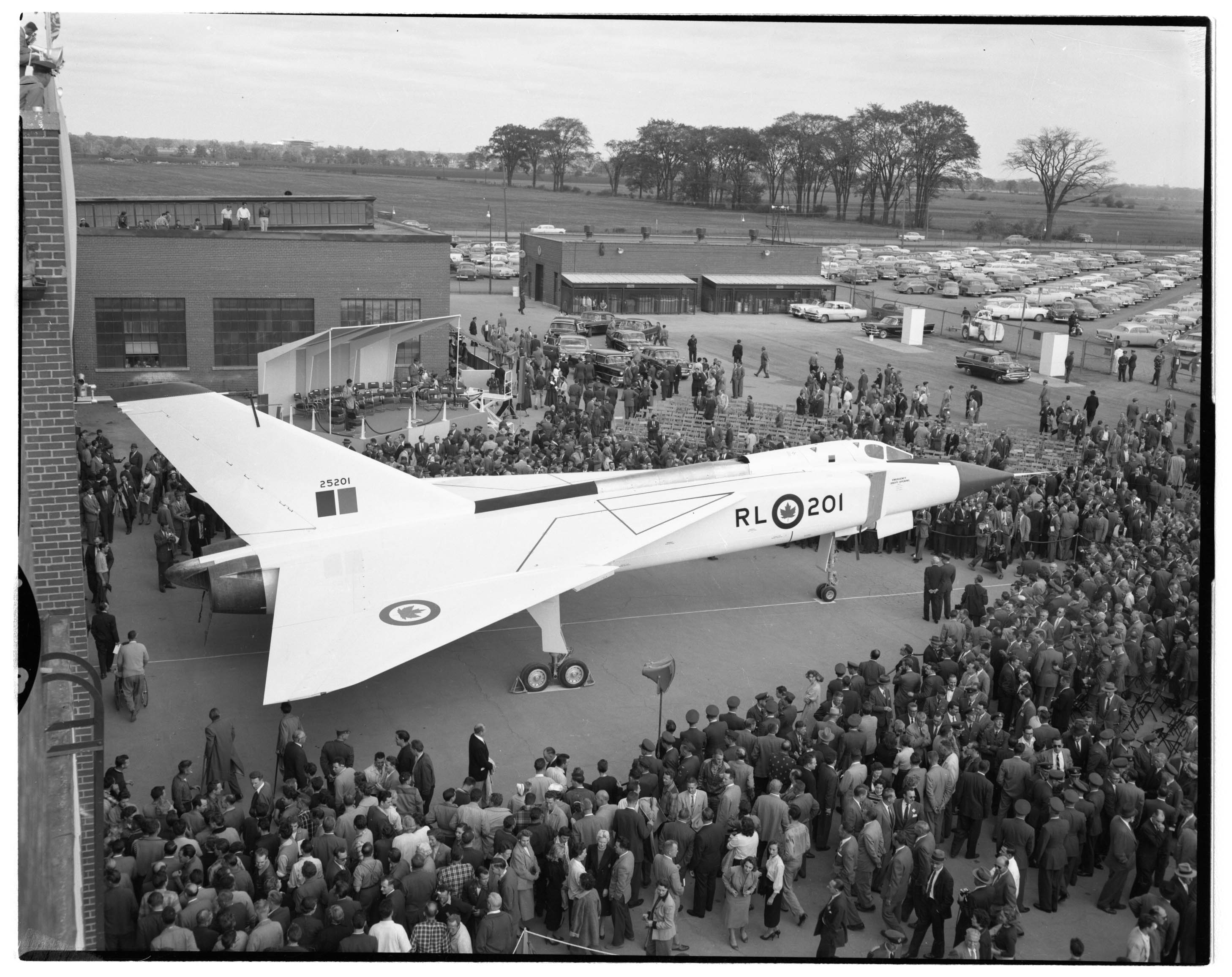 Photo noir et blanc d'une foule de personnes autour d'un aéronef blanc.
