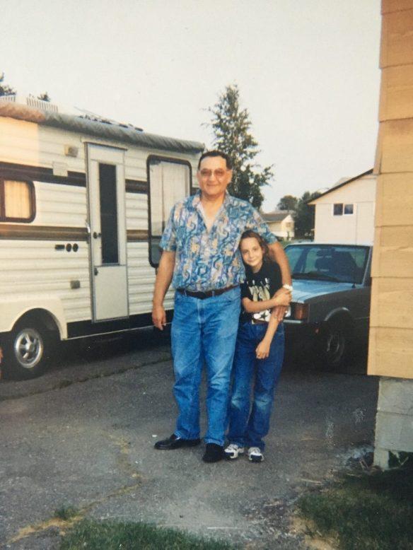 Photographie couleur d'un homme et d'une jeune fille souriants, posant devant une caravane blanche et une voiture.