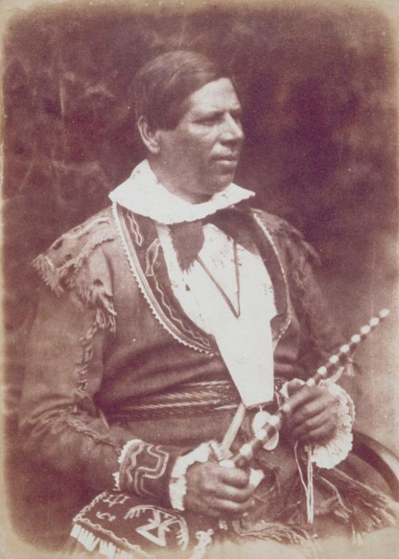 Photo sépia d'un homme assis, tenant une pipe de cérémonie et un collier de perles wampum. L'homme est vêtu d'une veste en peau de cerf; sur sa cuisse, on aperçoit un sac (également en peau de cerf) orné de motifs traditionnels.