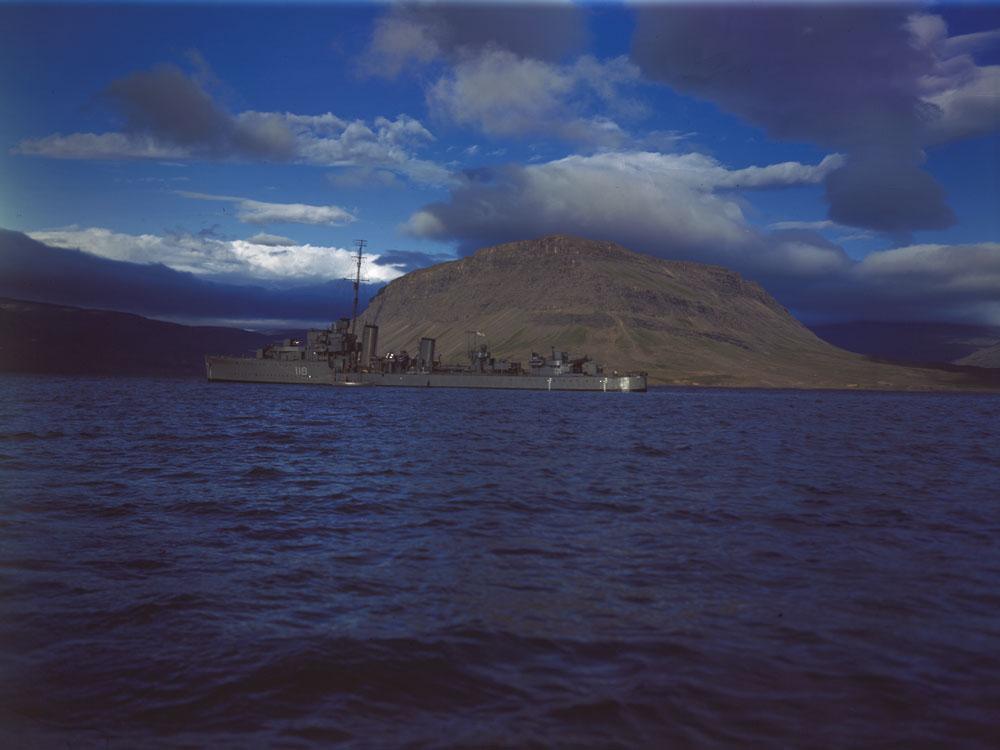 Photographie couleur d'un grand navire devant une île.