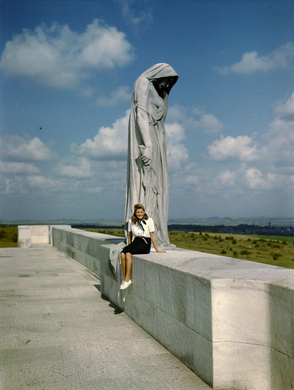 Photographie en couleur d'une jeune femme portant une blouse blanche et une jupe foncée, assise devant une grande statue représentant une femme en deuil.
