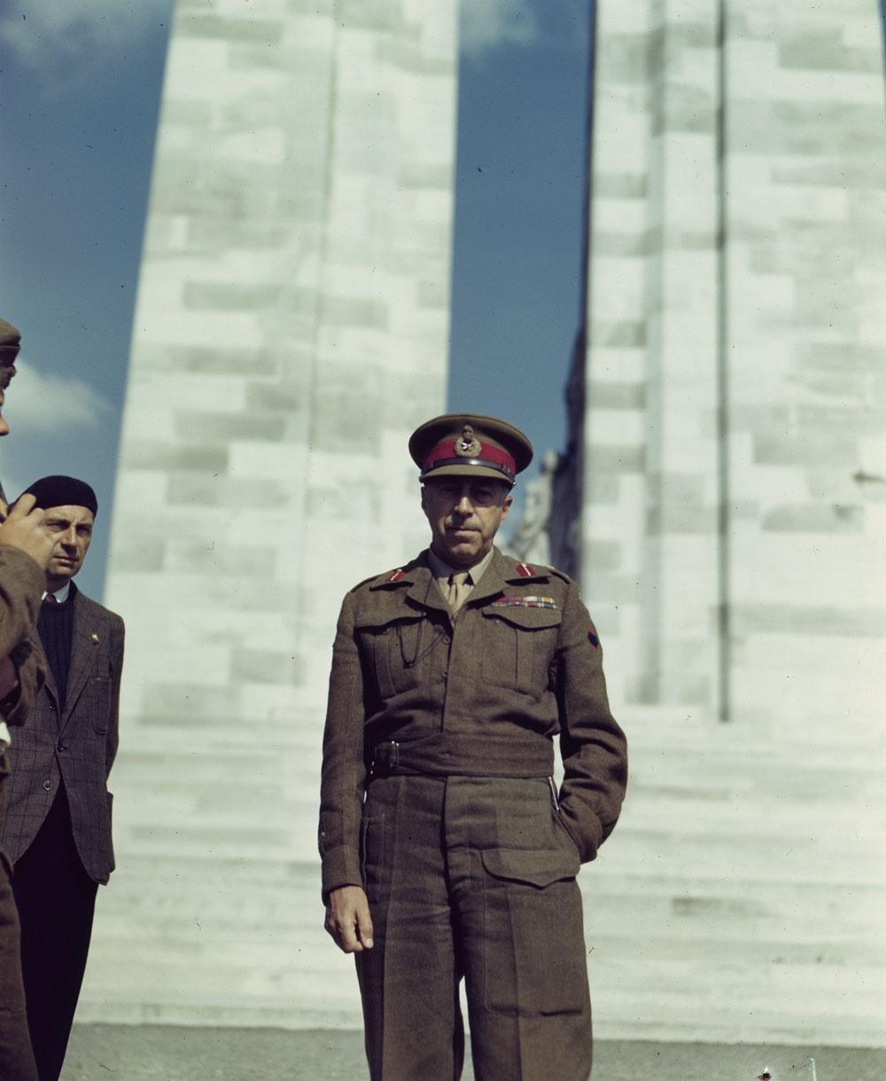 Photographie en couleurs d'un militaire en uniforme debout devant un monument commémoratif de guerre en maçonnerie. Juste à gauche, un homme portant un veston en tweed et un béret est partiellement visible.