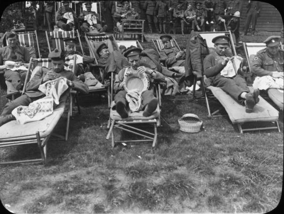 Photo noir et blanc de soldats en uniforme, assis dehors en train de tricoter.