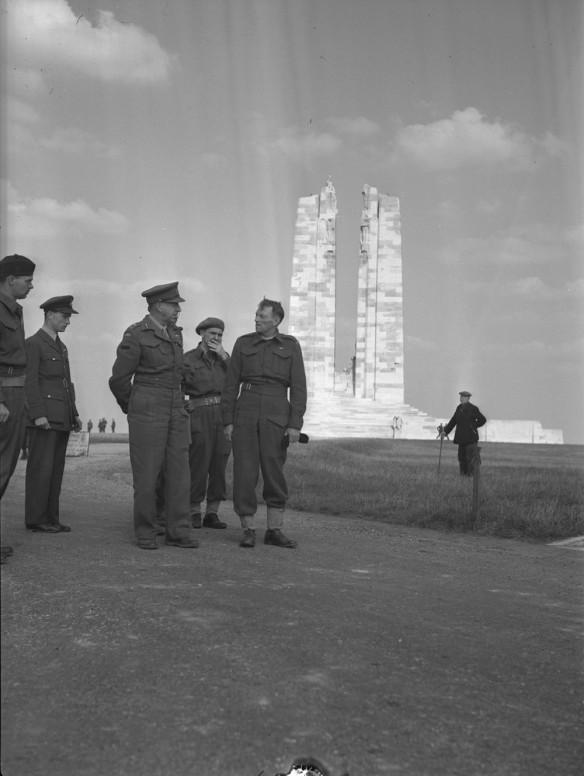 Un groupe d'hommes en uniforme militaire discutent, sous les yeux d'un civil se tenant au loin. À l'arrière-plan se dressent les deux hautes colonnes d'un mémorial de guerre en maçonnerie.