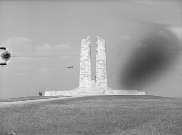 Photographie noir et blanc montrant un petit avion volant près d'un mémorial de guerre en maçonnerie caractérisé par deux hautes colonnes.