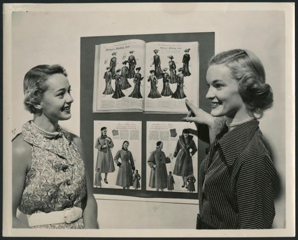 Photo noir et blanc de deux femmes, visage souriant, devant deux catalogues de mode, l'un de la fin du 19e siècle, l'autre du milieu du 20e siècle.