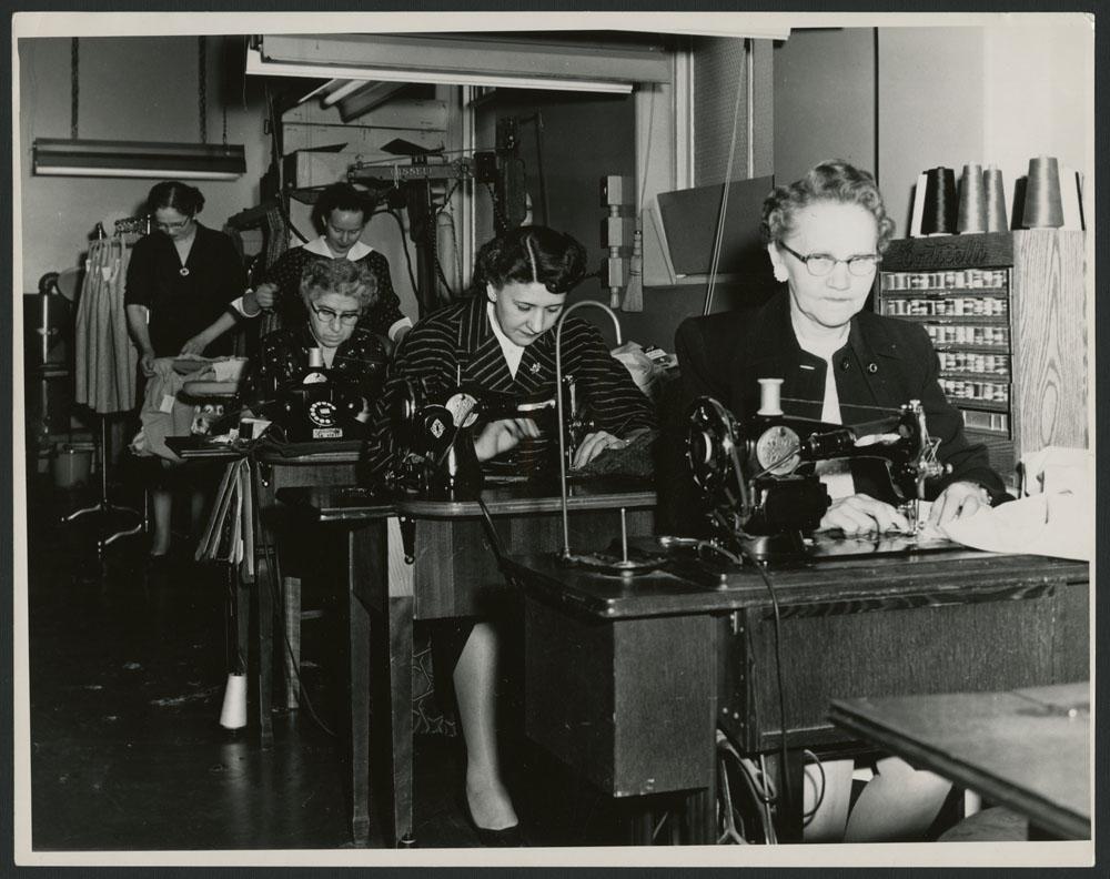 Photo noir et blanc montrant deux repasseuses et trois couturières.