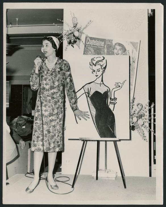 Photo noir et blanc montrant une femme qui parle au micro, devant un grand dessin de mode posé sur chevalet.