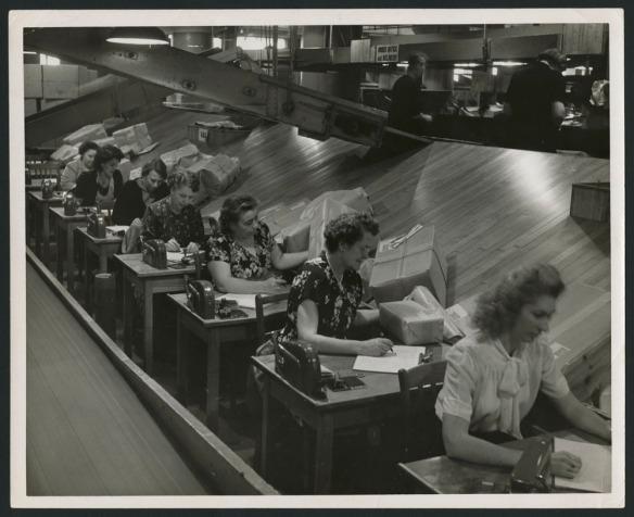 Deux photos noir et blanc. La première montre le personnel triant des paquets dans des bacs. L'autre montre des employées vérifiant les adresses sur des paquets; les paquets glissent vers elles en descendant une rampe.