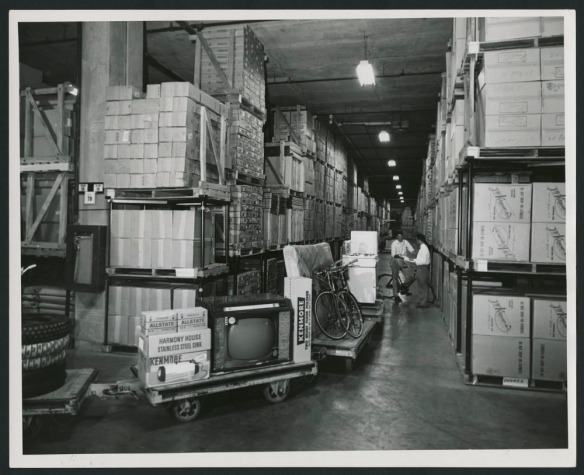 Photo noir et blanc montrant deux employés en train de vérifier des documents dans un grand centre de distribution éclairé au néon. À l'avant-plan, on voit un train de chariots chargés de produits.