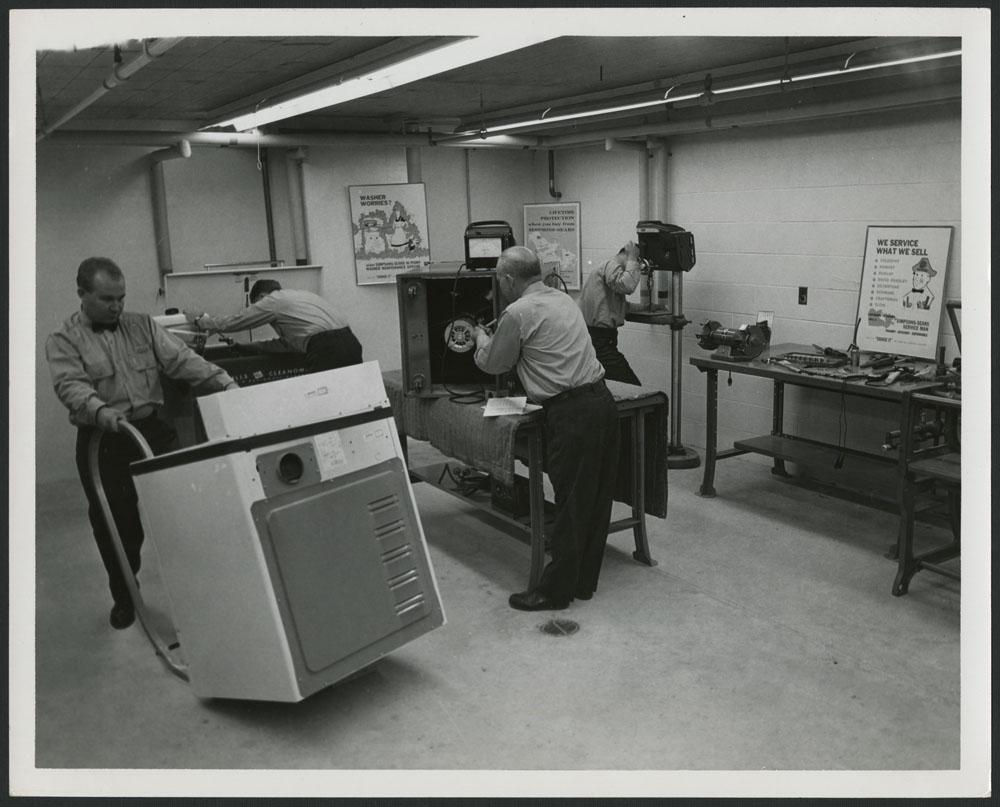 Photo noir et blanc montrant trois employés réparant des appareils dans un atelier; un quatrième employé déplace un gros appareil.