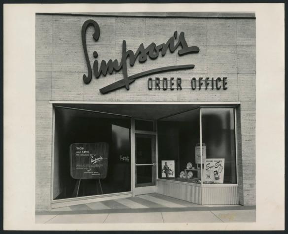 Photo noir et blanc de la façade d'un magasin de vente par catalogue. Au haut de la façade, on voit l'enseigne « Simpson's Order Office »; des affiches publicitaires sont placées en vitrine.