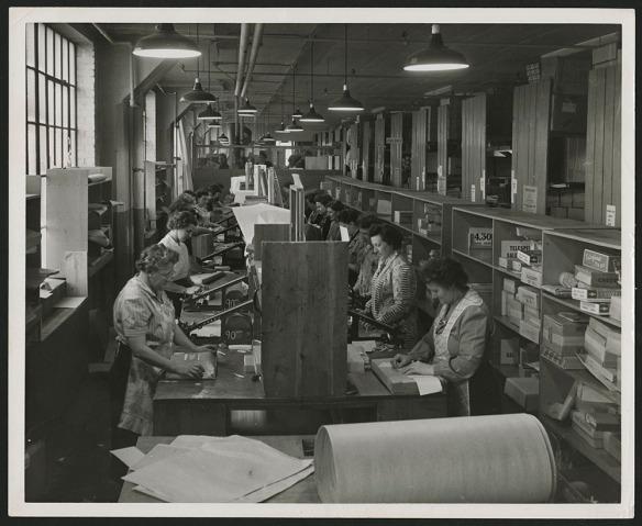 Photo noir et blanc montrant deux rangées de postes debout, où des femmes en tablier emballent des paquets sur un long comptoir. Derrière elles, on voit des étagères remplies de paquets. À l'avant-plan, on voit un grand rouleau de papier à emballer.