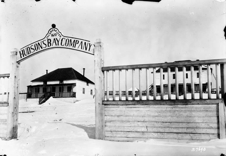 Photo noir et blanc d'un bâtiment derrière un portail sur lequel on peut lire « Compagnie de la Baie d'Hudson, constituée en 1670 ». Un deuxième bâtiment est partiellement caché par une clôture du côté droit.