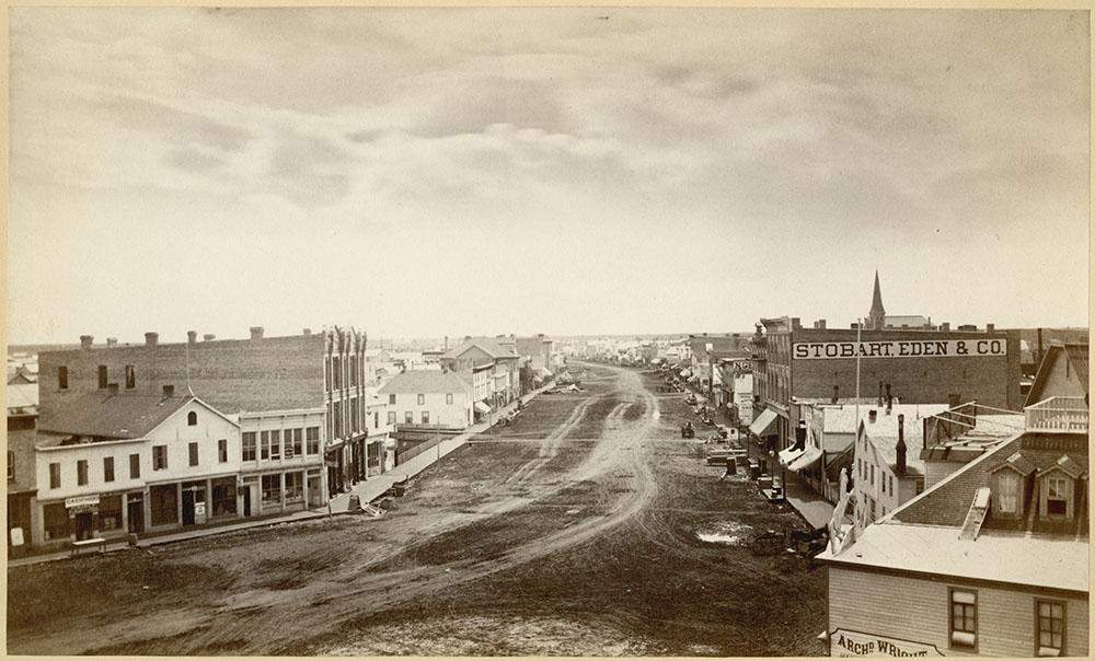 Photographie en sépia d'une petite ville où des bâtiments se dressent de chaque côté d'une large rue de terre marquée de traces de charrettes.