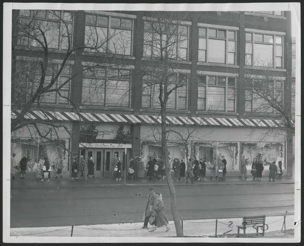 Photo noir et blanc montrant des clients devant de grandes vitrines décorées pour Noël et se dirigeant vers l'entrée principale d'un magasin Simpson's. Des enseignes au-dessus des portes indiquent « Simpson's » et « The Christmas Tree Store » (Boutique d'arbres de Noël).