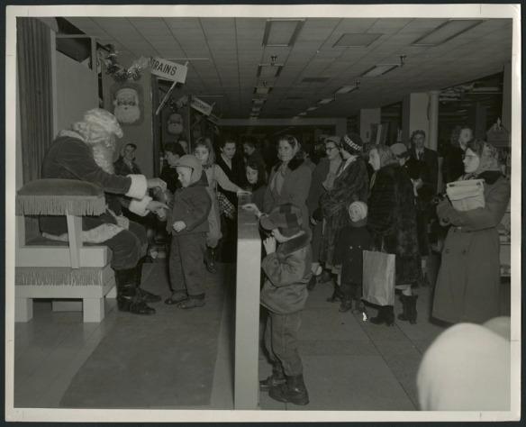 Photo noir et blanc montrant un garçon parlant avec le père Noël alors que d'autres enfants et de nombreux parents, vêtus pour affronter l'hiver, font la file à proximité. En arrière-plan, deux affiches disent « Trains » et « Meccano ».