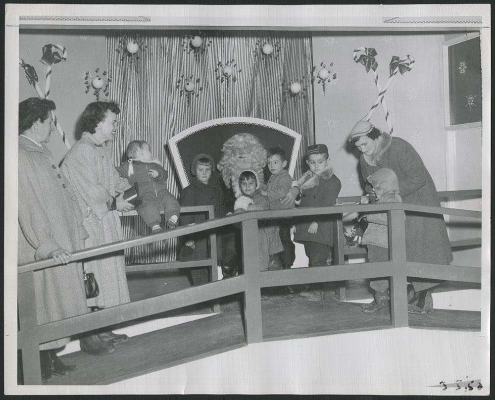 Photo noir et blanc montrant des enfants et trois femmes autour d'un père Noël. Tout le monde sourit, même si certains enfants semblent nerveux.