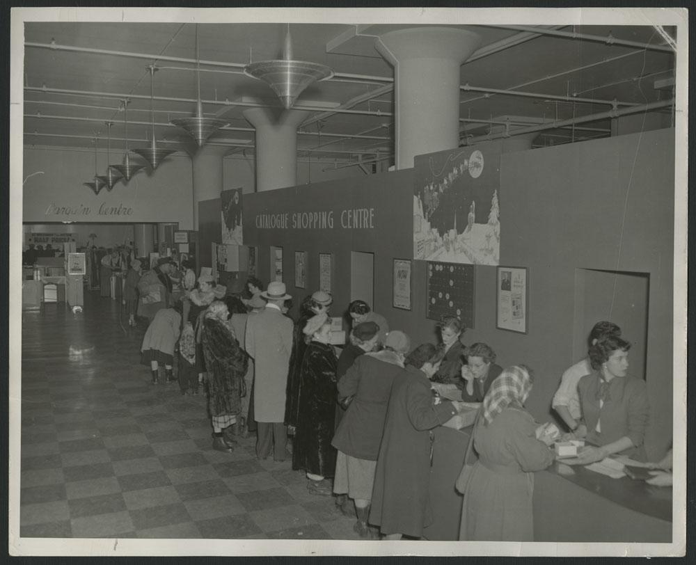 Photo noir et blanc montrant des clients, surtout des femmes, avec des manteaux d'hiver et des chapeaux. Elles consultent des catalogues pendant que des employés se tiennent derrière le comptoir. Une inscription sur le mur, entourée de décorations de Noël, dit : « Catalogue Shopping Centre » (Centre de ventes par catalogue).