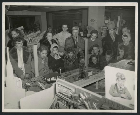 Photo noir et blanc montrant un grand groupe d'hommes, de femmes et d'enfants regardant un train électrique dans un magasin.