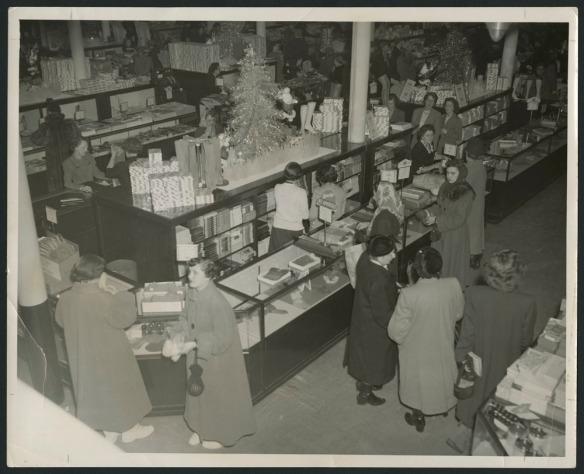 Photo noir et blanc montrant un grand magasin bondé et décoré pour Noël. Des clientes et des employées se trouvent au comptoir des bas, des collants et des accessoires.
