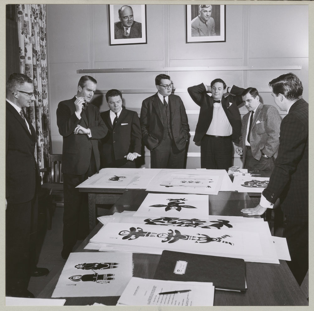 Photo noir et blanc de sept hommes en complet, debout en train de regarder des œuvres étalées sur une table.
