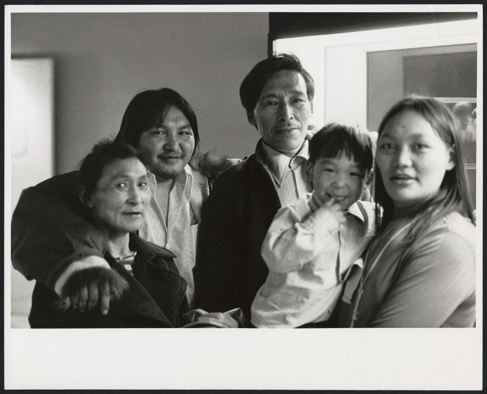 Photo noir et blanc de quatre adultes et d'un enfant souriant à la caméra.