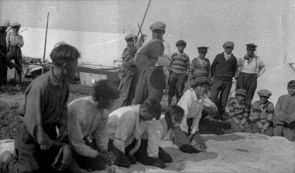 Photo composite noir et blanc montrant une quinzaine de garçons jouant aux jeux de mains dénés, debout ou agenouillés au sol. Un jeune homme debout frappe un tambour en peau de caribou avec une baguette de bois.