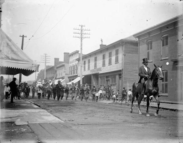 Une foule défile au milieu d'une rue dans une petite ville. Des magasins en bois bordent la rue de chaque côté. La foule est menée par un homme noir distingué, moustachu, vêtu d'un haut-de-forme et d'une queue-de-pie, qui se déplace à cheval. Une fanfare, des groupes de petits garçons et plusieurs adultes marchent derrière lui. La plupart des gens dont le visage est visible dans la foule semblent Noirs. En arrière-plan, un deuxième cheval tire un char sur lequel se tiennent des femmes vêtues de robes blanches et de chapeaux à large bord.