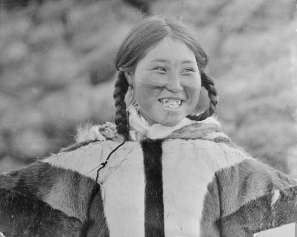 Photographie noir et blanc d'une femme inuk qui sourit. Elle porte des tatouages au visage.
