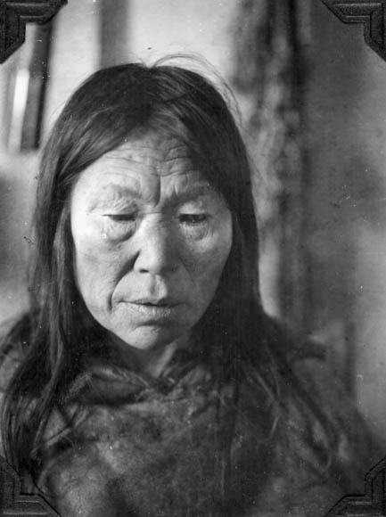 Photographie noir et blanc d'une Inuk portant un parka de fourrure.