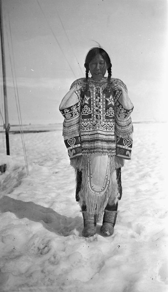Photographie noir et blanc d'une femme inuk debout dans la neige, portant un parka orné.