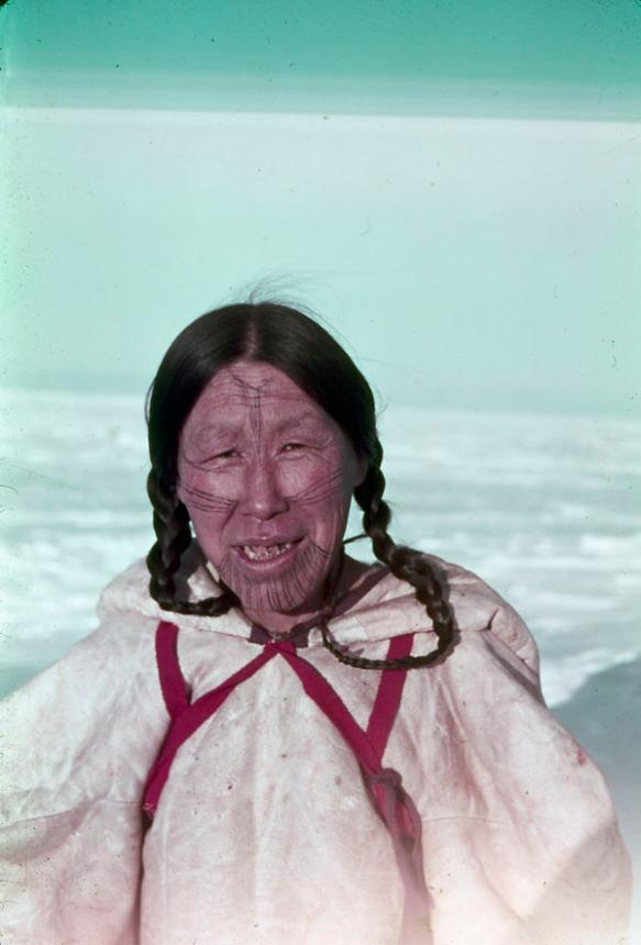 Photographie couleur d'une femme inuk arborant des tatouages faciaux et portant un parka blanc avec des courroies rouges.
