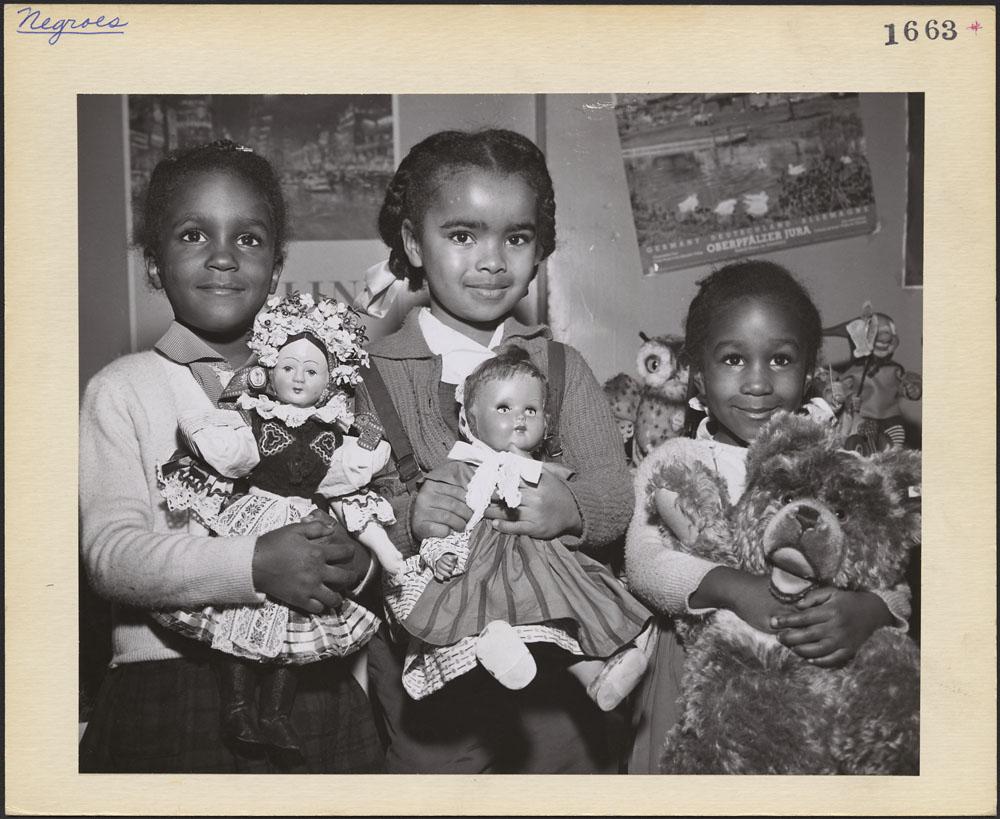 Photographie noir et blanc de trois petites filles noires tenant des jouets. Les deux fillettes à gauche tiennent des poupées de porcelaine, et celle à droite, un gros ourson en peluche. Les trois enfants sourient timidement au photographe et aux passants. Elles sont bien habillées, ont les cheveux coiffés en tresses décorées de rubans, et se tiennent debout devant un mur couvert d'affiches.