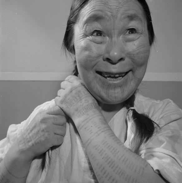 Photographie noir et blanc d'une Inuk arborant des tatouages sur le visage et les bras, tressant ses cheveux en souriant