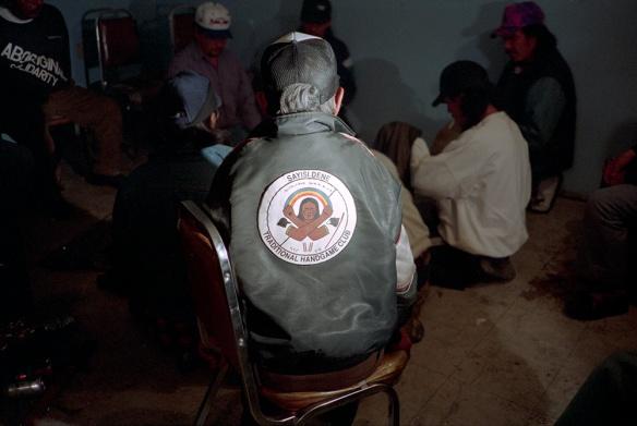 Photo couleur d'un homme âgé vu de dos, regardant une partie de jeux de mains dénés. Il porte une veste avec l'inscription « Sayisi Dene Traditional Handgame Club » (Club de jeux de mains traditionnels des Dénés sayisi).