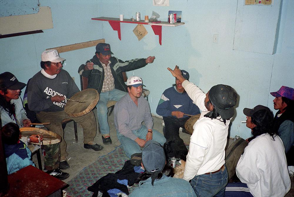 Photo couleur de huit hommes et d'un bambin. Les hommes jouent à des jeux de mains dénés. Trois d'entre eux frappent des tambours en peau de caribou avec des baguettes de bois. Deux autres font des signes propres aux jeux de mains dénés.