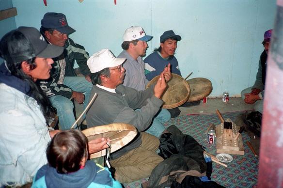 Photo couleur de six hommes et d'un bambin. Les hommes jouent aux jeux de mains dénés. Trois d'entre eux chantent en frappant des tambours en peau de caribou avec des baguettes de bois.